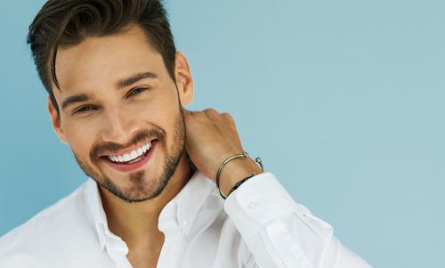 Younger man smiling with facial hair l Dental implants smyrna ga