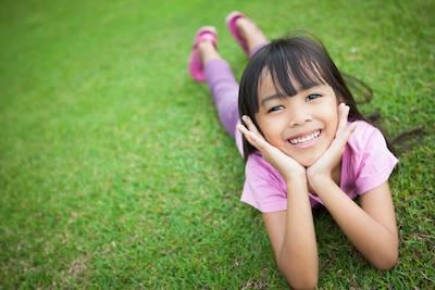 Young girl smiling laying on grass l dental exams smyrna ga