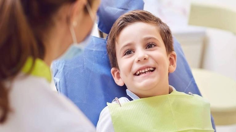 young boy sitting in dental exam chair smiling l family dentistry smyrna ga